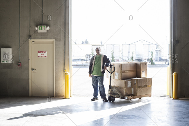 Male warehouse worker standing next to a manual pallet jack and cardboard boxes in a distribution warehouse