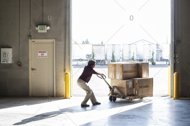 A female warehouse worker moving products in cardboard boxes by using a manual pallet jack in a distribution warehouse