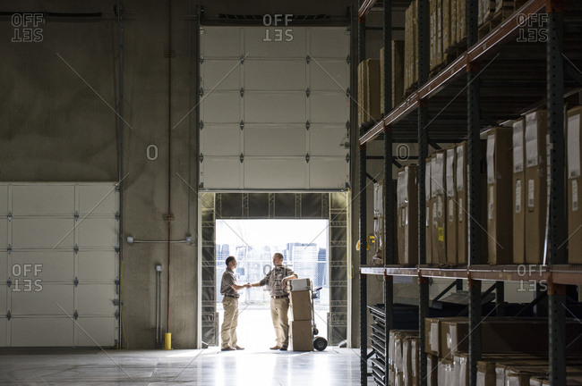 Two warehouse workers shaking hands while standing in the doorway of a loading dock in a large distribution warehouse