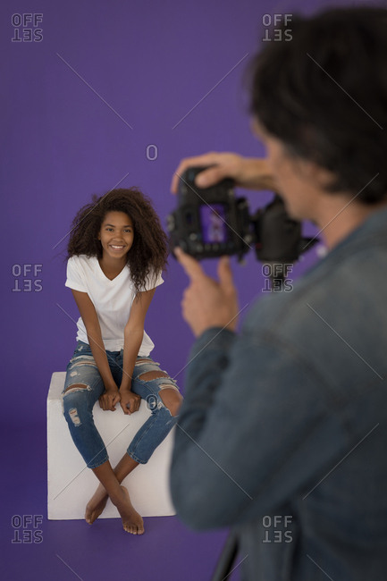 Professional Photographer taking picture of model in studio