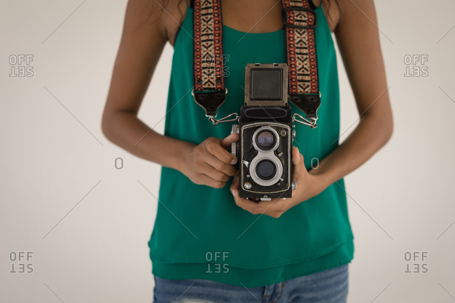 Mid section of female Photographer standing with digital camera