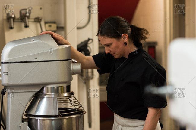 Chef using whisking machine in commercial kitchen