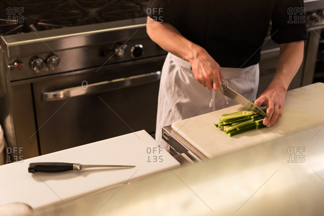 Mid section of chef chopping vegetable in the kitchen