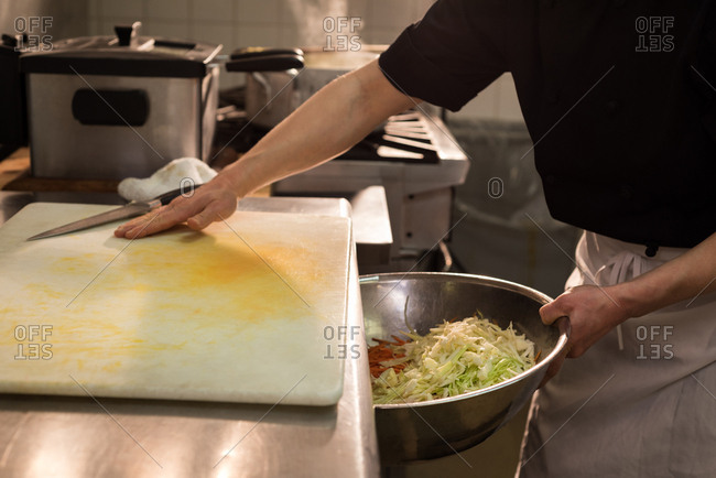 Chef putting chopped vegetables into the big bowl in kitchen