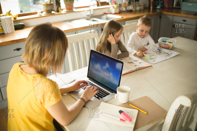 Siblings drawing while mother working on laptop in kitchen at home