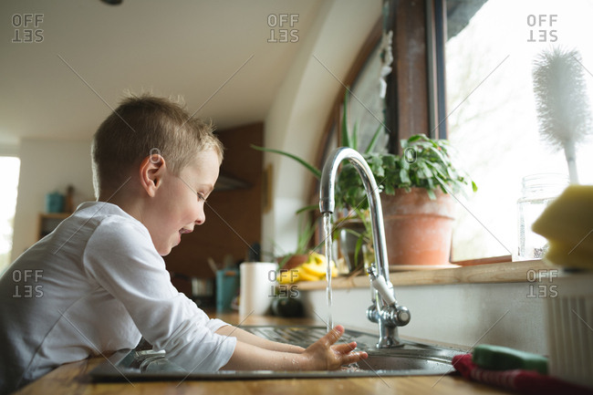 Boy washing hands on kitchen sink at home