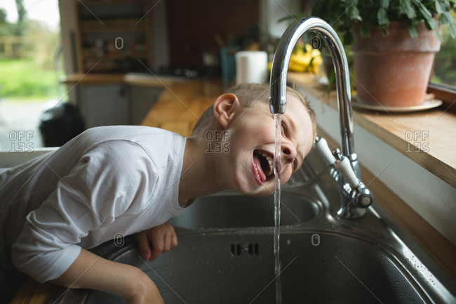 Young boy drinking water from tap in kitchen at home