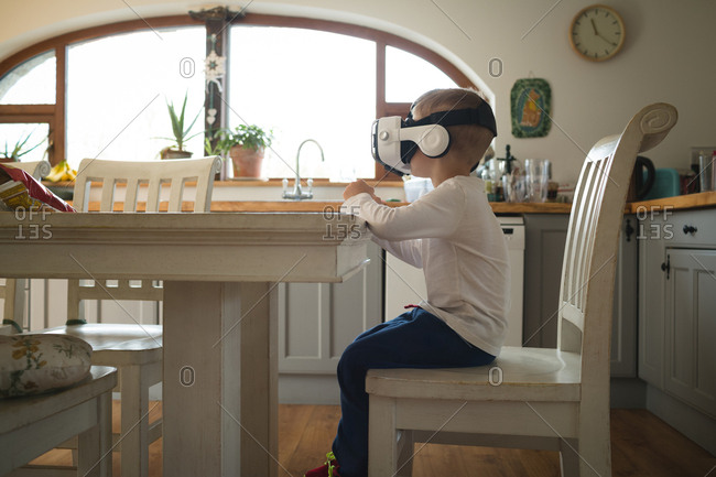 Male child experiencing virtual reality headset in kitchen at home