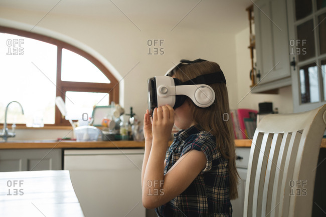 Female child experiencing virtual reality headset in kitchen at home