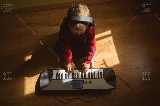 Little boy playing piano in bedroom at home