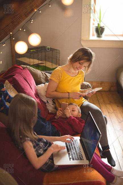 Family on sofa using multimedia devices at home