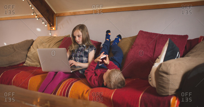 Sibling using multimedia devices on sofa at home