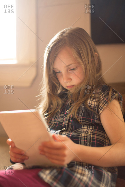 Girl sitting on sofa and using digital tablet at home