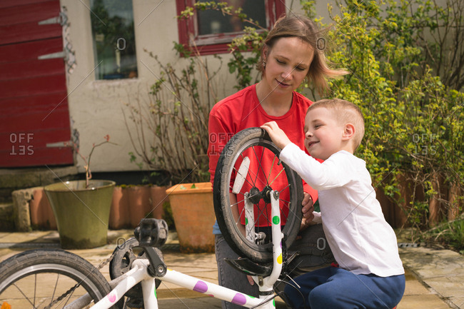 Mother and son repairing bicycle together at backyard