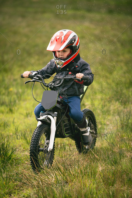 Close-up of kid rider riding a bike in garden