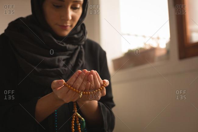 Close-up of muslim woman with prayer beads praying at home
