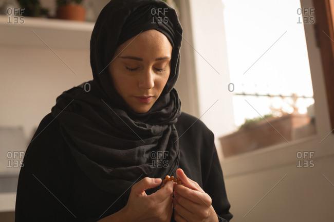 Muslim woman praying with prayer beads at home
