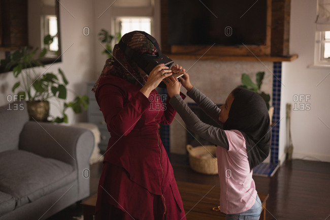Muslim mother and daughter using VR headset at home
