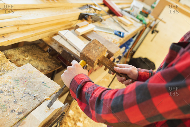 Male carpenter using chisel with hammer in workshop