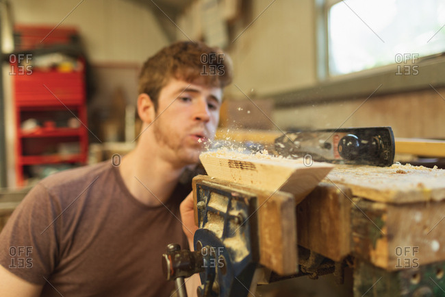 Young male carpenter blowing wood shavings in workshop