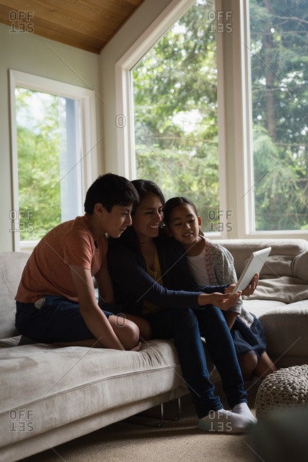 Mother and kids having video call on laptop in living room at home