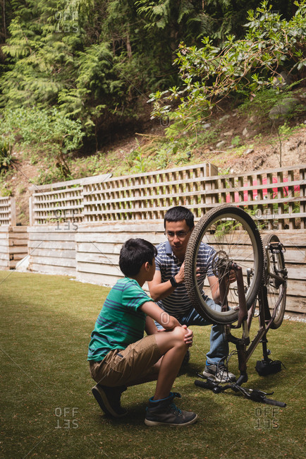 Father and son interacting with each other while repairing cycle in the garden