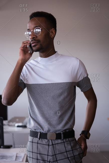 Young office executive talking on mobile phone in the office