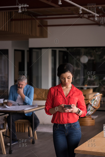 Beautiful office executive using mobile phone at creative office