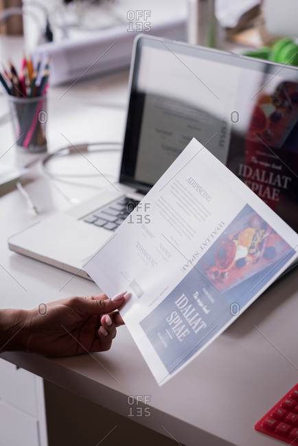 Close-up of businessperson holding a brochure at desk