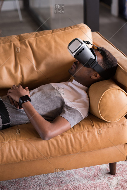 Young man experiencing VR headset while lying on sofa