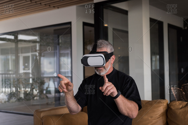 Male office executive experiencing virtual reality headset on sofa at creative office