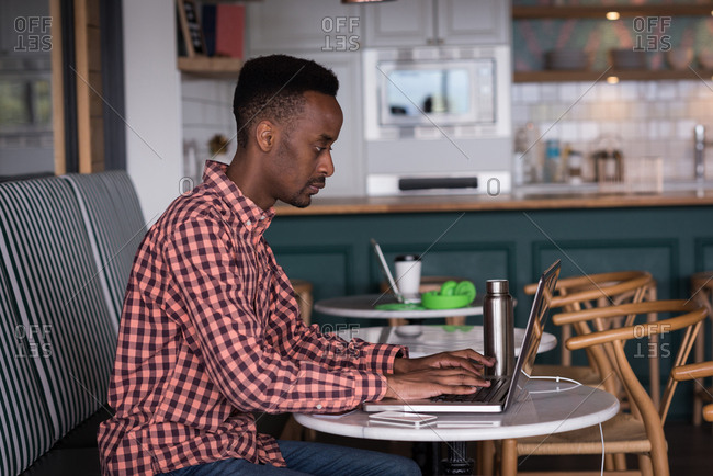 Male office executive using laptop in cafeteria at creative office