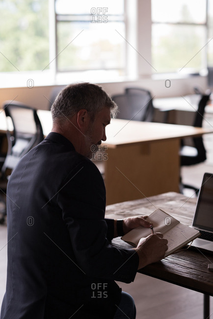 Businessman writing on diary on desk at creative office