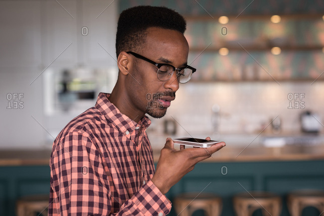 Male office executive talking on mobile phone in cafeteria at creative office