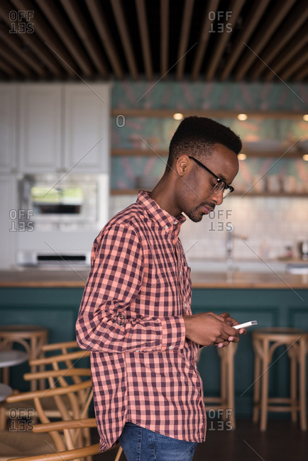 Male office executive using mobile phone in cafeteria at creative office