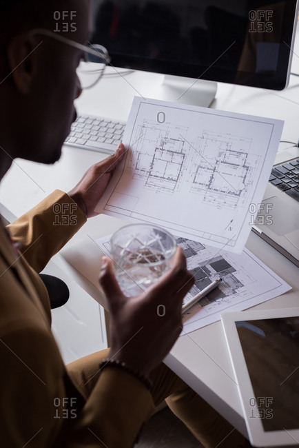 Close-up of male office executive checking blueprint on desk at creative office