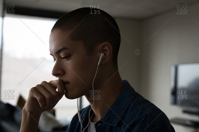 Young man listening music on earphones at home