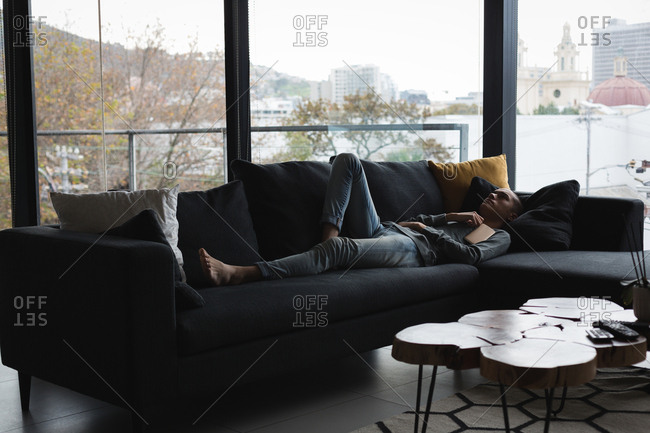 Young man sleeping in living room at home