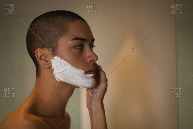 Young man applying shaving cream on his face in bathroom