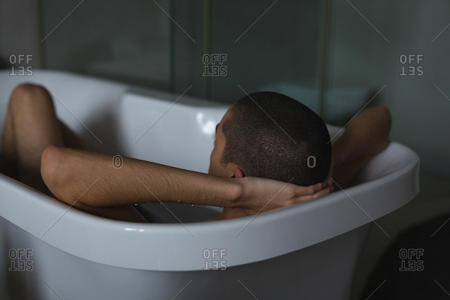 Young man relaxing in bathtub at bathroom