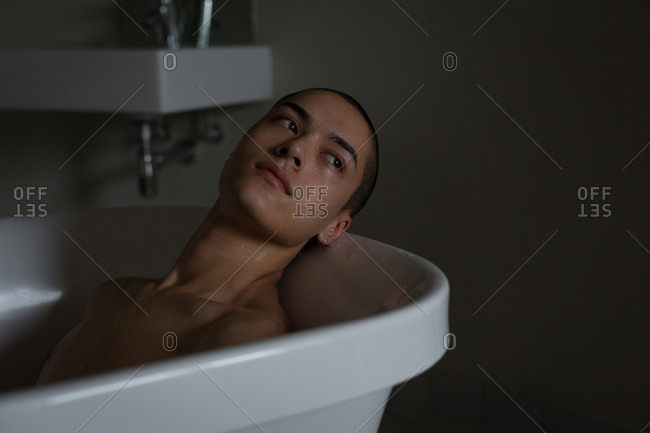 Thoughtful young man relaxing in bathtub at bathroom