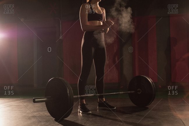 Woman rubbing powder on hand before barbell workout in gym