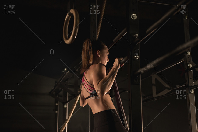 Side view of woman doing pull-ups at the gym