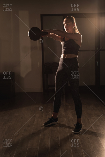 Woman doing exercises with kettlebell in gym