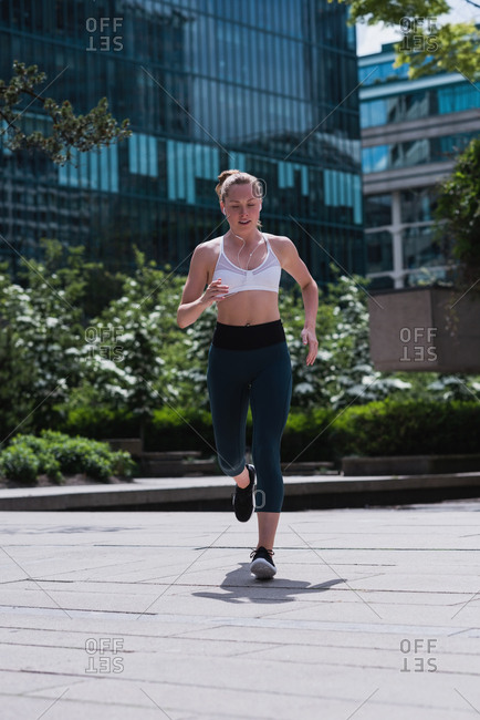 Young sporty woman jogging on street