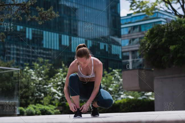 Young sporty woman tying shoe laces
