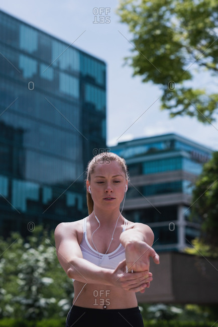 Young sporty woman stretching on street