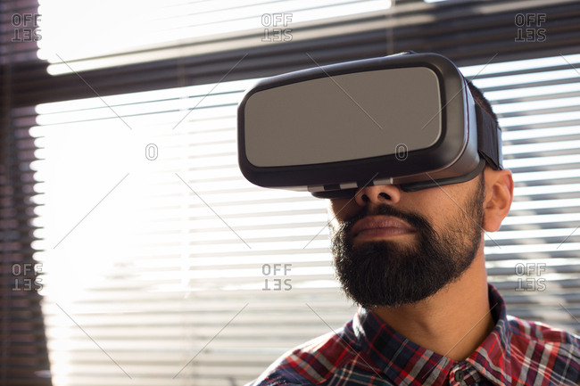 Male executive using virtual reality headset in office