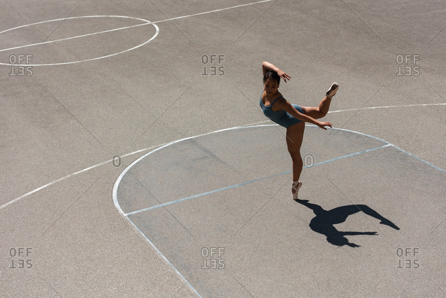 Young female ballet dancer dancing in the basketball court