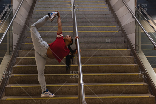 Young female street dancer dancing on staircase